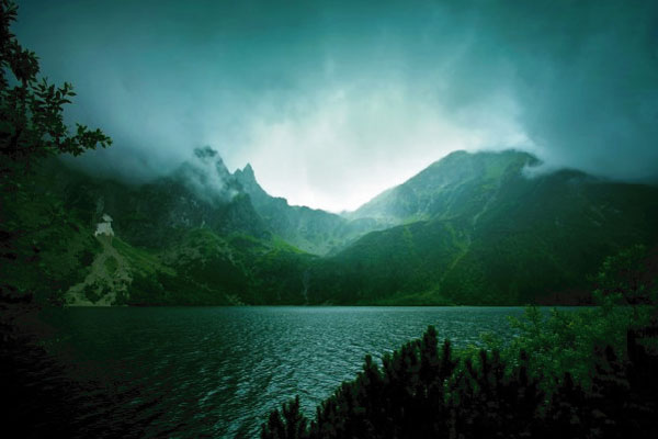 Lake in front of a lush mountain surrounded by mist and dark trees